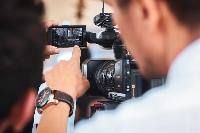 Chargé de production vidéo vérifiant le cadrage d'une prise